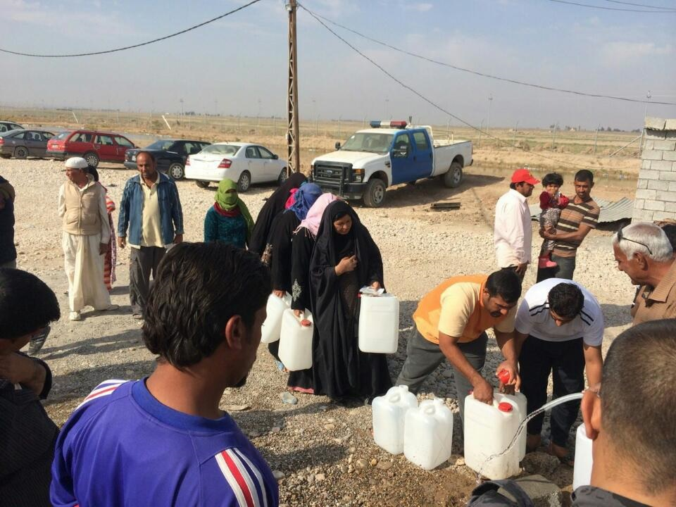 Iraqi civilians line up to get fresh water from Rainfresh's water treatment system